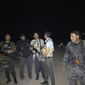 In this image made with a mobile phone, Iraqi security forces and tribal fighters gather for a patrol in central Ramadi, Iraq, early Friday, April 17, 2015.  In Iraq's western Anbar province, Iraqi special forces maintained control of the provincial capital, Ramadi, after days of intense clashes with the Islamic State group left the city at risk. Sabah Nuaman, a special forces commander in Anbar, said the situation had improved early Friday after airstrikes hit key militant targets on the city's fringes. (AP Photo)