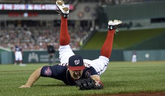 Washington Nationals first baseman Ryan Zimmerman (11) lays out on the ground after he caught a bunt pop up in foul territory by Philadelphia Phillies' Sean O'Sullivan for an out during the fifth inning of a baseball game, Friday, April 17, 2015, in Washington. (AP Photo/Nick Wass)