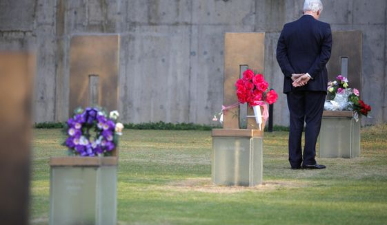 Former President Bill Clinton stands in the Field of Empty Chairs at the chair of Oklahoma City bombing victim Alan G. Whicher,of the U.S. Secret Service, after lying a bouquet of flowers on the chair during a visit to the Oklahoma City National Memorial in Oklahoma City. (AP Photo/Bryan Terry, Pool)