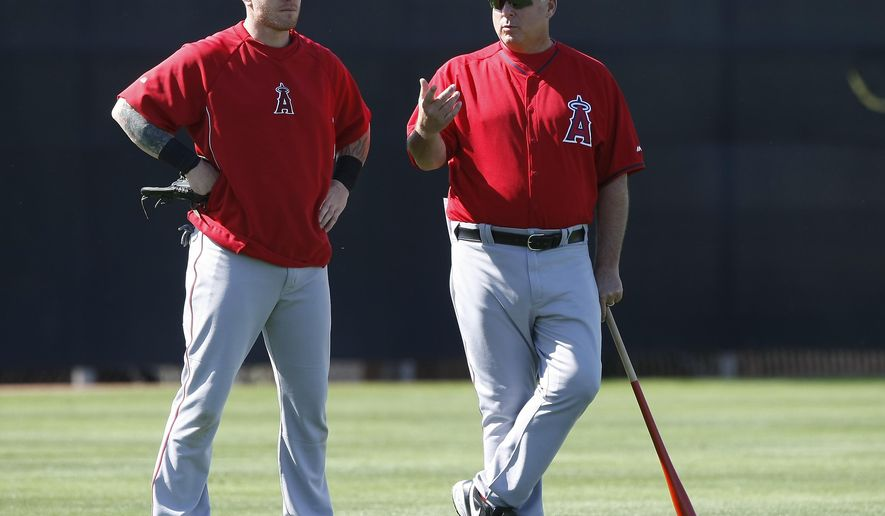"""FILE - In this Feb. 20, 2014, file photo,Los Angeles Angels left fielder Josh Hamilton, left, talks to manager Mike Scioscia during spring training baseball practice in Tempe, Ariz. Scioscia says he's """"really confident"""" about having some communication with Josh Hamilton when the team is in Houston, where the slugger has been rehabbing from shoulder surgery. Scioscia didn't say Wednesday, April 15, 2015, if that would include a face-to-face meeting.(AP Photo/Rick Scuteri), File"""