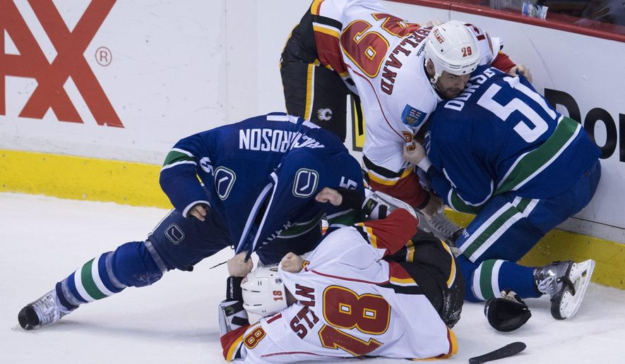 Vancouver Canucks' Brad Richardson (15) fights with Calgary Flames' Matt Stajan (15) as Vancouver Canucks right wing Derek Dorsett (51) fights with Calgary Flames defenseman Deryk Engelland (29) during the third period of Game 2 of an NHL hockey first-round playoff series, Friday, April 17, 2015, in Vancouver, British Columbia. (Jonathan Hayward/The Canadian Press via AP)
