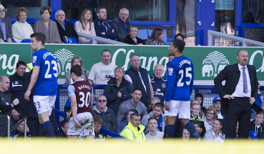 Burnley's Ashley Barnes, second left, walks from the pitch after being sent off by referee Mike Jones during the English Premier League soccer match between Everton and Burnley at Goodison Park Stadium, Liverpool, England, Saturday April 18, 2015. (AP Photo/Jon Super)