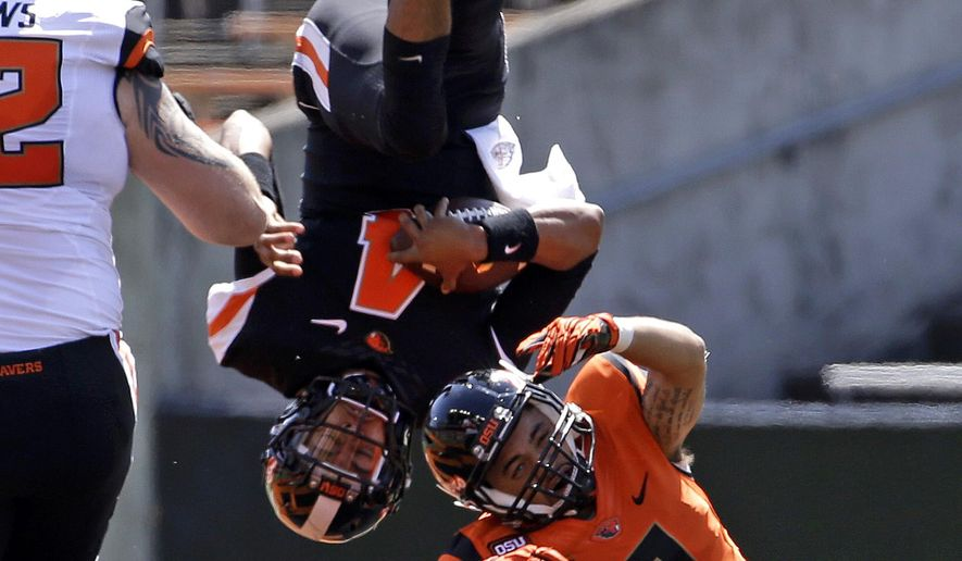 Oregon State quarterback Seth Collins (4) is upended by orange squad defender Dashon Hunt (9) during the first half of their NCAA college football spring game in Corvallis, Ore., Saturday, April 18, 2015. (AP Photo/Don Ryan)