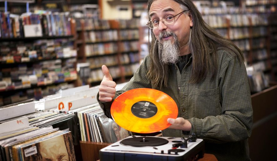 """FILE- In this April 19, 2012 file photo, Chris Bown poses  in Scarborough, Maine, with a copy of The Knack's """"Live in Los Angeles 1978.""""  Brown from Maine-based Bull Moose music hatched the idea for the annual event to celebrate local record stores, and the first one was held seven years ago. It's grown to more than 2,200 participating stores on Saturday, April 18, 2015.  (AP Photo/Robert F. Bukaty)"""