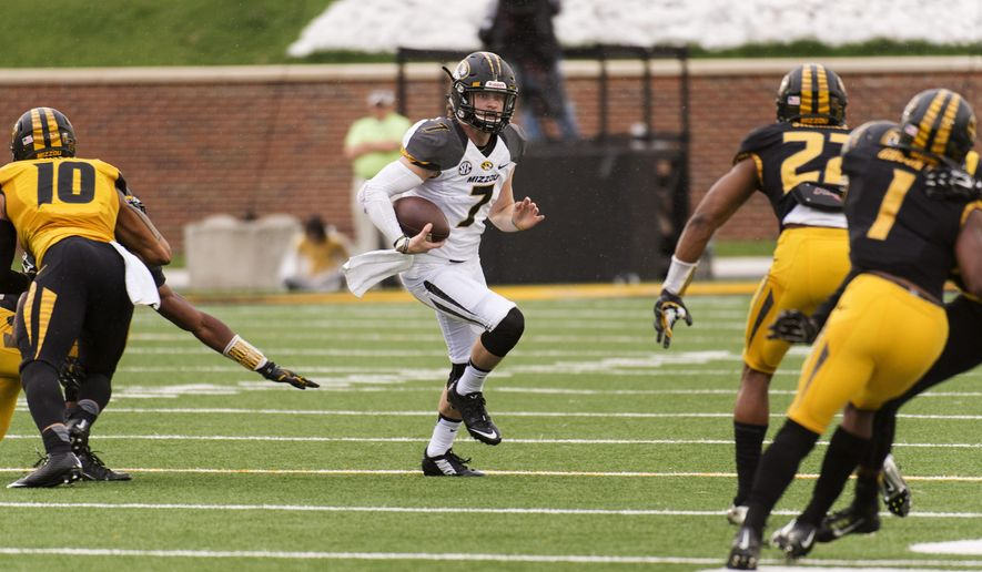 Missouri quarterback Maty Mauk, center, splits defenders as he runs upfield during an NCAA college spring football game Saturday, April 18, 2015, in Columbia, Mo. (AP Photo/L.G. Patterson)