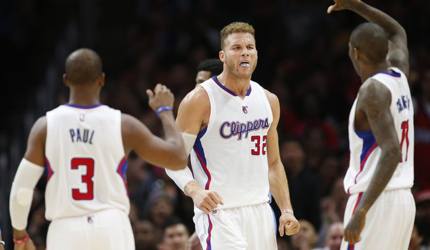 Los Angeles Clippers' Blake Griffin, center, celebrates with teammates Chris Paul, left, and Jamal Crawford, right, after scoring while being fouled by Denver Nuggets' Kenneth Faried, during the second half of an NBA basketball game, Monday, April 13, 2015, in Los Angeles. The Clippers won 110-103. (AP Photo/Danny Moloshok)