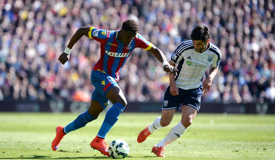 West Bromwich Albion's Claudio Yacob, right, challenges Crystal Palace's Wilfried Zaha during their English Premier League soccer match at Selhurst Park, London, Saturday, April 18, 2015. (Jon Buckle/PA via AP)      UNITED KINGDOM OUT      -     NO SALES     -     NO ARCHIVES