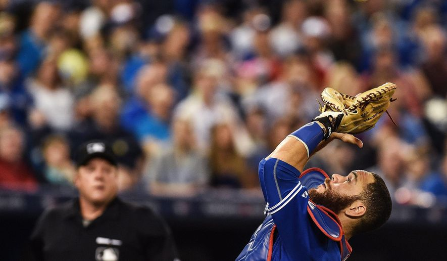 Toronto Blue Jays catcher Russell Martin catches a pop out hit by Atlanta Braves' Andrelton Simmons during the fourth inning of a baseball game in Toronto, Saturday, April 18, 2015. (Aaron Vincent Elkaim/The Canadian Press via AP)   MANDATORY CREDIT