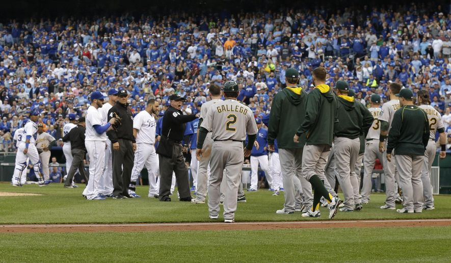 Umpires get between the Oakland Athletics and Kansas City Royals after benches emptied after Oakland Athletics' Brett Lawrie was hit by a pitch during the fourth inning of a baseball game at Kauffman Stadium in Kansas City, Mo., Saturday, April 18, 2015. (AP Photo/Orlin Wagner)