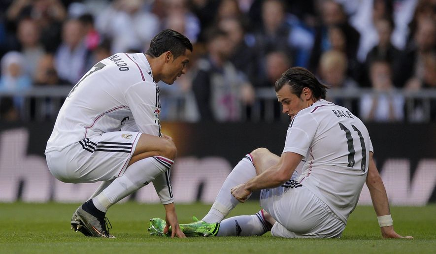 Real Madrid's Gareth Bale, right, gestures to teammate Cristiano Ronaldo after he got injured during a Spanish La Liga soccer match between Real Madrid and Malaga at the Santiago Bernabeu stadium in Madrid, Spain, Saturday, April 18, 2015. (AP Photo/Andres Kudacki)