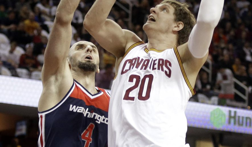 Cleveland Cavaliers' Timofey Mozgov (20), from Russia, shoots over Washington Wizards' Marcin Gortat (4), from Poland, in the first quarter of an NBA basketball game Wednesday, April 15, 2015, in Cleveland. (AP Photo/Mark Duncan)