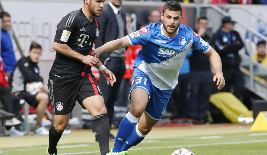 Hoffenheim's Kevin Volland, right, and Bayern's Juan Bernat from Spain, challenge for the ball during a German first division Bundesliga soccer match between TSG 1899 Hoffenheim and Bayern Munich in Sinsheim, Germany, Saturday, April 18, 2015. (AP Photo/Michael Probst)