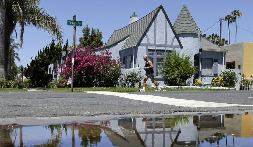 A house is reflected in a puddle of water from an irrigated front yard in San Diego. State regulators on Saturday, April 18, 2015  announced a revised plan to reduce water use in drought-stricken California that offers easier conservation targets for major cities, including Los Angeles, while demanding greater cutbacks from others. The new water reduction targets released by the State Water Resources Control Board responds to criticisms from cities that said earlier targets were unrealistic and unfair. Recognizing that some communities are farther along than others in conservation, the water board released a draft plan last week that requires varying levels of cutbacks for cities to ensure enough water if dry conditions persist. (AP Photo/Gregory Bull, File)