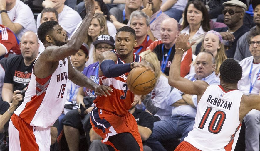 Washington Wizards' Bradley Beal, center, lays off a pass as Toronto Raptors' Amir Johnson (15) and DeMar DeRozan defend during the second half in Game 1 in the first round of the NBA basketball playoffs, Saturday, April 18, 2015,  in Toronto. The Wizards won 93-86 in overtime.  (Chris Young/The Canadian Press via AP)   MANDATORY CREDIT