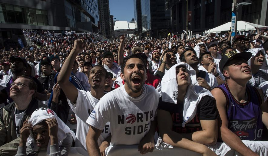 Fans cheer in Maple Leaf Square cheer as they watch a televised broadcast of the Toronto Raptors play against Washington Wizards in Game 1 of the NBA basketball playoffs in Toronto, Saturday, April 18 , 2015. (Chris Young/The Canadian Press via AP)   MANDATORY CREDIT