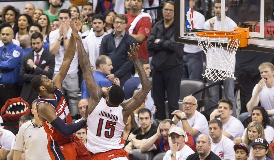 Washington Wizards' John Wall, left, shoots over Toronto Raptors' Amir Johnson during overtime in Game 1 in the first round of the NBA basketball playoffs, Saturday, April 18, 2015,  in Toronto. The Wizards won 93-86 in overtime.  (Chris Young/The Canadian Press via AP)   MANDATORY CREDIT