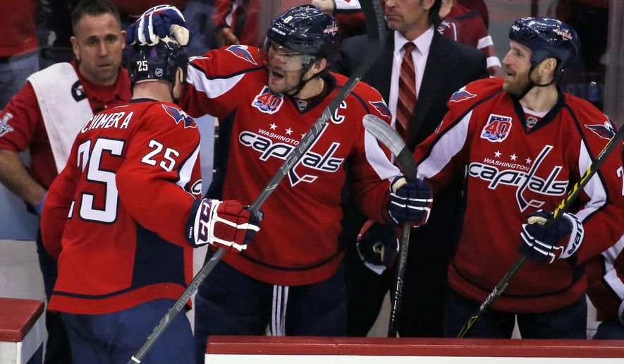 Washington Capitals left wing Jason Chimera (25) celebrates with left wing Alex Ovechkin (8), from Russia, and center Brooks Laich (21) after Chimera's goal during the third period against the New York Islanders in Game 2 of a first-round NHL hockey playoff series, Friday, April 17, 2015, in Washington. The Capitals won 4-3. (AP Photo/Alex Brandon)