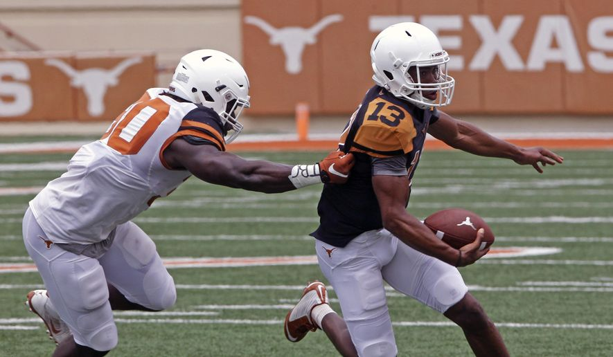Texas quarterback Jerrod Heard, right, runs against linebacker Timothy Cole, left, during the first quarter of Texas' Orange and White spring NCAA college football game, Saturday, April 18, 2015, in Austin, Texas. (AP Photo/Michael Thomas)