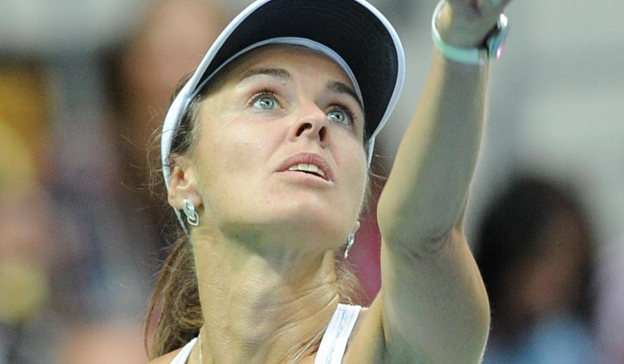 Switzerland's Martina Hingis serves  a  ball  to Poland's Agnieszka Radwanska during their Fed Cup World Group Playoff tennis match between Poland and Switzerland, in Zielona Gora, Poland, Saturday, April 18, 2015.  Five-time Grand Slam champion Martina Hingis  played  her first competitive singles match since 2007.   (AP Photo/Alik Keplicz)