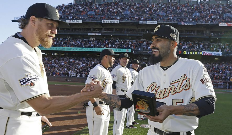 San Francisco Giants' Hunter Pence, left, shakes hands with Sergio Romo during the 2014 World Series championship ring ceremony before the Giants' baseball game against the Arizona Diamondbacks on Saturday, April 18, 2015, in San Francisco. (AP Photo/Ben Margot, Pool)