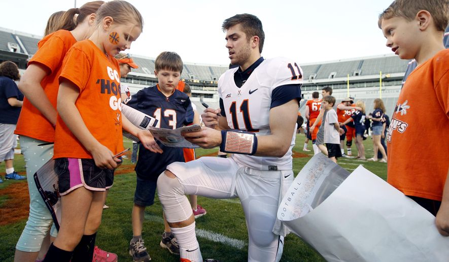 Virginia quarterback Greyson Lambert (11) signs autographs after the annual spring NCAA college football game held Saturday, April 18, 2015, at Scott Stadium in Charlottesville, Va. (Andrew Shurtleff/The Daily Progress via AP)