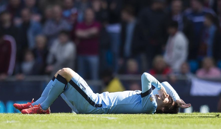 Manchester City's David Silva lies on the pitch before being carried off injured during his team's English Premier League soccer match between Manchester City and West Ham United at the Etihad Stadium, Manchester, England, Sunday April 19, 2015. (AP Photo/Jon Super)