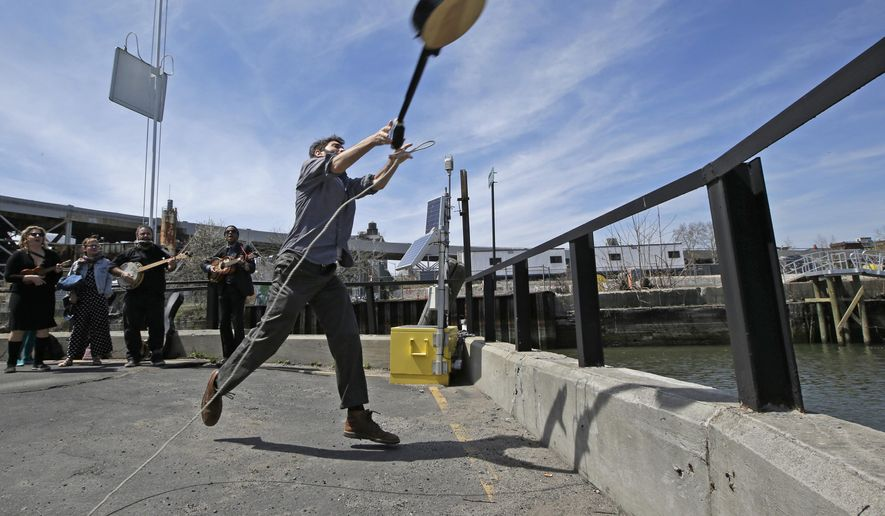 """Event founder, banjo player and folk music promoter Eli Smith tosses a banjo during the fifth annual Brooklyn Folk Festival's Gowanus Banjo Toss, Sunday, April 19, 2015, in the Brooklyn borough of New York. About two dozen people participated in the annual event. Smith who conceived the event said, """"I love the banjo, but sometimes I have the perverse desire to see it thrown into a body of water."""" (AP Photo/Kathy Willens)"""