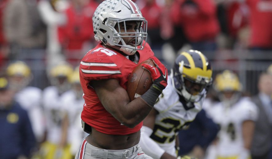 FILE - In this Nov. 29, 2014, file photo, Ohio State running back Ezekiel Elliott carries the ball against Michigan during an NCAA college football game in Columbus, Ohio. Elliott won the AAU Sullivan Award on Sunday, April 19, 2015, as the most outstanding U.S. amateur athlete who also demonstrates premier leadership, character and sportsmanship. (AP Photo/Jay LaPrete, File)