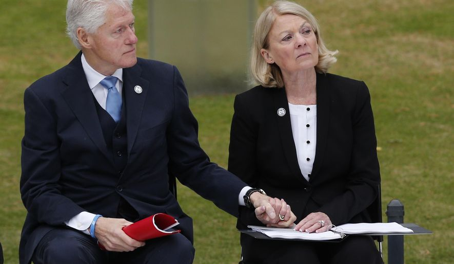 Former President Bill Clinton, left, holds the hand of former state Rep. Susan Winchester, right, the chairman of the the Oklahoma City National Memorial Foundations, during a ceremony for the 20th anniversary of the Oklahoma City bombing at the Oklahoma City National Memorial in Oklahoma City, Sunday, April 19, 2015. Winchester lost her sister Dr. Peggy Clark in the bombing. (AP Photo/Sue Ogrocki)