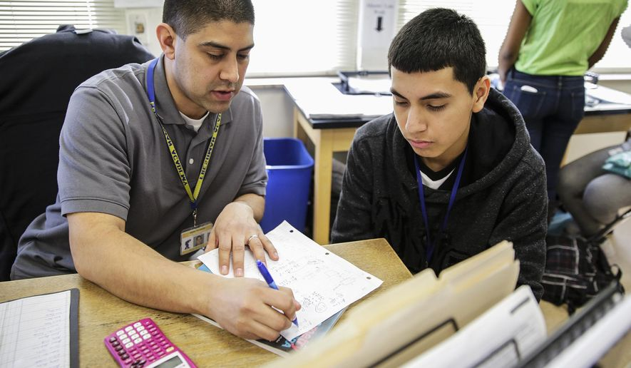 In this March 11, 2015 photo, Joliet Central High School math teacher Israel Velazquez, left, works with freshman Abraham Rodriguez, 14, during an accelerated math class in Joliet Ill. Velazquez, a former accountant and Chicago middle-school teacher, said the support class tries to meet each student's ability level and bring them as close to the ninth-grade level as possible.  (Lathan Goumas/The Herald-News via AP)  CHICAGO TRIBUNE OUT, MANDATORY CREDIT