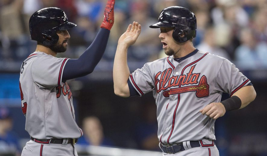Atlanta Braves Nick Markakis, left, and Chris Johnson celebrate after scoring on a Jonny Gomes three-run double during first-inning baseball game action against the Toronto Blue Jays in Toronto on Sunday, April 19, 2015. (Darren Calabrese/The Canadian Press via AP) MANDATORY CREDIT