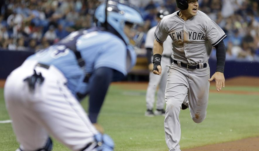 New York Yankees' Jacoby Ellsbury, right, races home to score on a sacrifice fly by teammate Mark Teixeira off Tampa Bay Rays starting pitcher Matt Andriese during the first inning of a baseball game Sunday, April 19, 2015, in St. Petersburg, Fla. Rays catcher Rene Rivera, left, looks on. (AP Photo/Chris O'Meara)