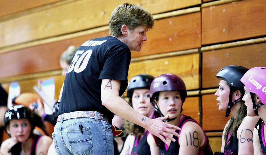 In this March 12, 2015 photo, Barbed Wire Betties Bench Coach Lee Clark talks to her team on the bench during a bout against the Illinois Valley Vixens at Huntley Middle School in DeKalb, Ill. Clark has recently returned from an eight-month stint in Antarctica as a 911 dispatcher. (Monica Synett/Daily Chronicle via AP)  CHICAGO TRIBUNE OUT, MANDATORY CREDIT
