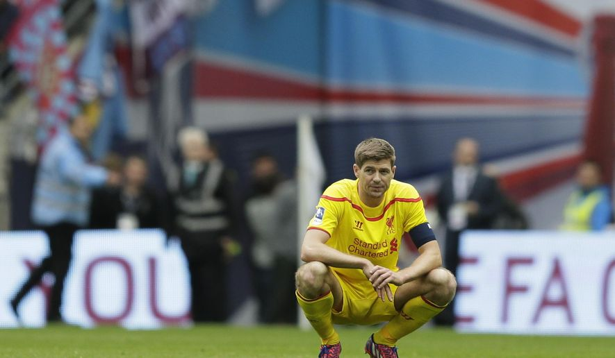 Liverpool's captain Steven Gerrard looks on as Aston Villa fans celebrate after the end f the English FA Cup semifinal soccer match between Liverpool and Aston Villa at Wembley Stadium in London, Sunday, April 19, 2015.  Aston Villa won the match 2-1 and will play Arsenal in the final. (AP Photo/Tim Ireland)