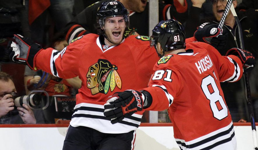 Chicago Blackhawks left wing Brandon Saad, left, celebrates with right wing Marian Hossa after scoring a goal during the second period in Game 3 of an NHL Western Conference hockey playoff series against the Nashville Predators, Sunday, April 19, 2015, in Chicago. (AP Photo/Nam Y. Huh)
