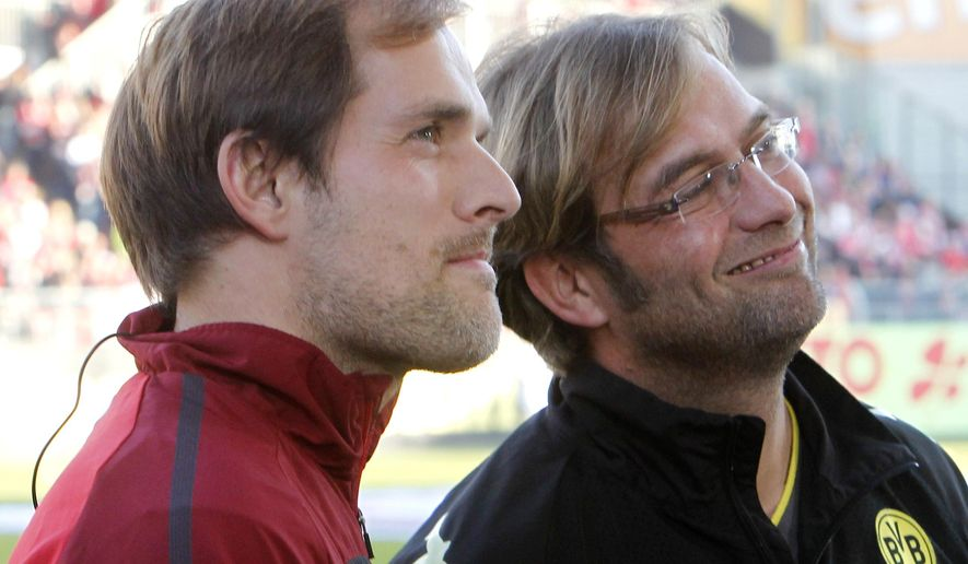 FILE - In this Oct. 31, 2010 file picture then Mainz's coach Thomas Tuchel, left, and Dortmund's coach Juergen Klopp stand together prior to the German first division Bundesliga soccer match between FSV Mainz 05 and Borussia Dortmund in Mainz,  Germany. Borussia Dortmund appointed Thomas Tuchel as coach with effect from the end of the season on Sunday April 19, 2015. The club said the former Mainz coach was getting a three-year contract effective from July 1. The 41-year-old Tuchel follows in the footsteps of Juergen Klopp, who announced his end-of-season departure on Wednesday, saying he was no longer the man for the job. Klopp previously coached Mainz. (AP Photo/Michael Probst.File)