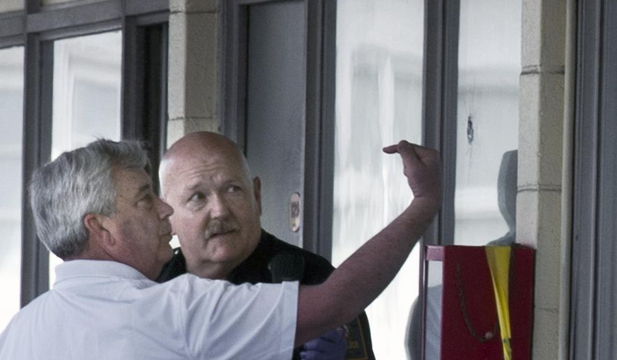 York County District Attorney Tom Kearney, left, points at what appears to be a bullet hole in the window of a hotel room at a Quality Inn, Sunday, April 19, 2015, in Springettsbury Township, Pa. Three people were found dead in the room, in what police say appears to be a double homicide-suicide. (Paul Kuehnel/York Daily Record via AP) YORK DISPATCH OUT