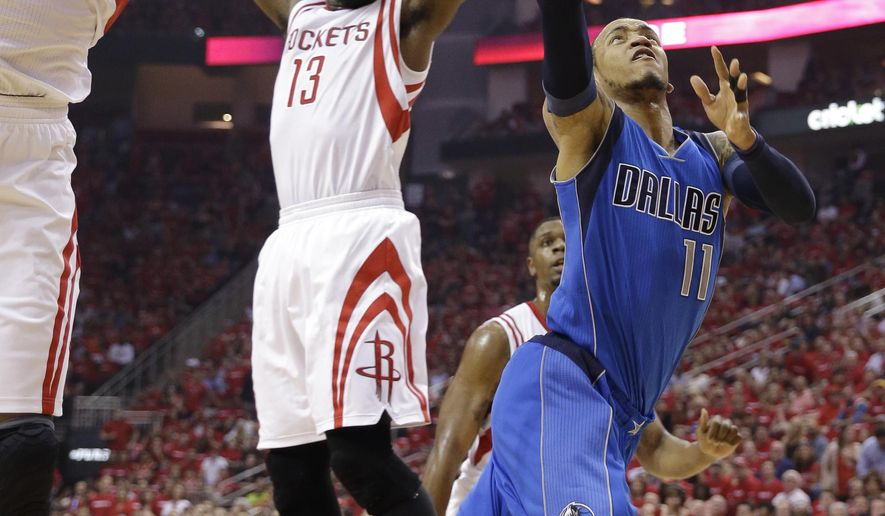 Dallas Mavericks' Monta Ellis (11) is blocked by Houston Rockets' Dwight Howard (12) as he tries to score during the first quarter of game 1 in the first round of the NBA basketball playoffs Saturday, April 18, 2015, in Houston. Houston Rockets' James Harden (13) also defends on the play. (AP Photo/David J. Phillip)