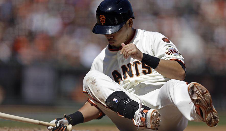 San Francisco Giants' Nori Aoki, of Japan, falls during an at-bat in the fifth inning of a baseball game against the Arizona Diamondbacks, Sunday, April 19, 2015, in San Francisco. (AP Photo/Ben Margot)