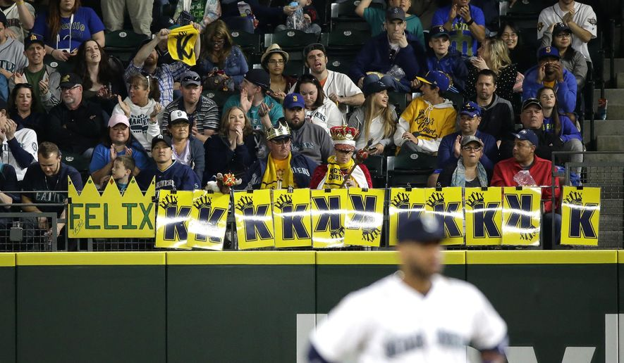 Fans sitting along the outfield rail in the seventh inning display 11 of the 12 strikeouts earned by Seattle Mariners starting pitcher Felix Hernandez in a baseball game against the Texas Rangers, Saturday, April 18, 2015, in Seattle. (AP Photo/Ted S. Warren)