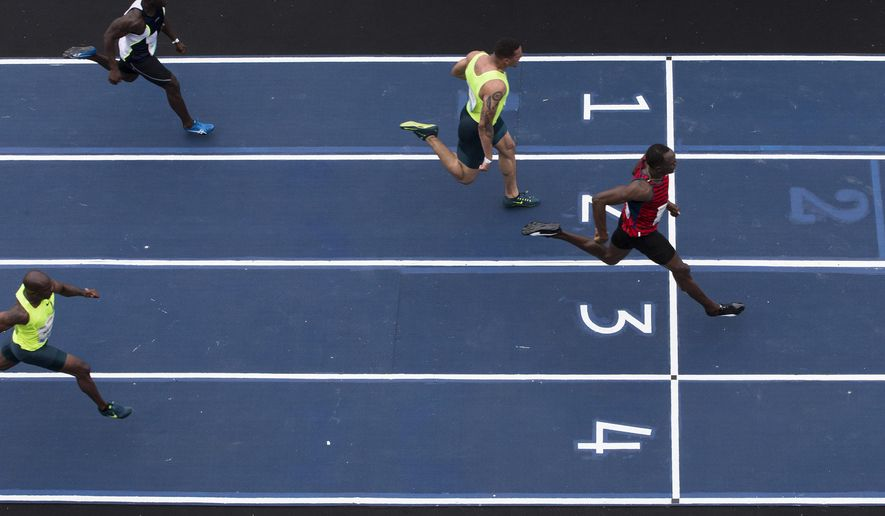 Jamaican sprinter Usain Bolt, right, runs against the United States' Ryan Bailey, lane 2, Brazil's Jose Carlos Moreira, lane 1, and Netherlands Churandy Martina, lane 4, during the 'Mano a Mano' challenge at the Jockey Club in Rio de Janeiro, Brazil, Sunday, April 19, 2015. Bolt won the 100m race. (AP Photo/Felipe Dana)