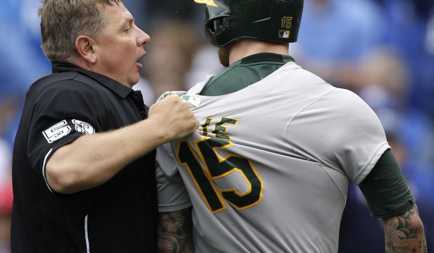 Home plate umpire Greg Gibson (53) holds back Oakland Athletics' Brett Lawrie (15) after he was thrown at during the eighth inning of a baseball game against the Kansas City Royals at Kauffman Stadium in Kansas City, Mo., Sunday, April 19, 2015. (AP Photo/Orlin Wagner)