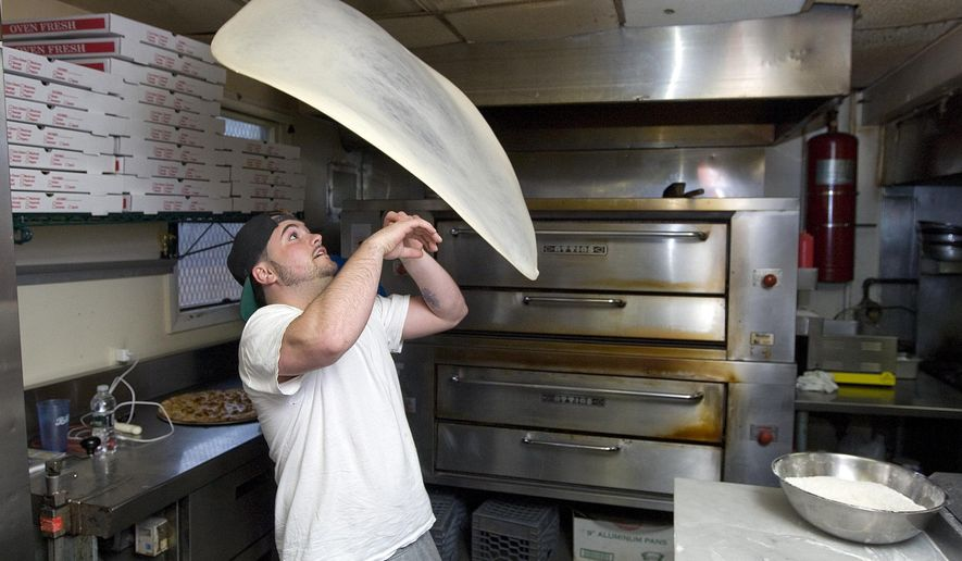 ADVANCE FOR WEEKEND OF APRIL 18, 2015, AND THEREAFTER- In this April 7, 2015, photo, Ace Memeti, manager of Formaggio Apizza Ristorante, twirls pizza dough in Southington, Conn. The restaurant placed third in a national pizza dough stretching competition in Las Vegas. (Dave Zajac/The Record-Journal via AP)