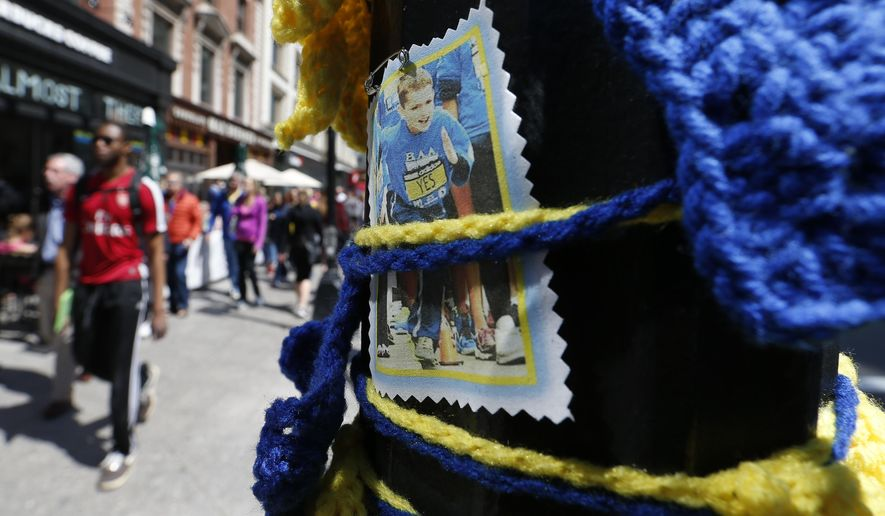 Pedestrians pass a photograph of Boston Marathon bombing victim Martin Richard, Saturday, April 18, 2015, in Boston, at the spot where the second bomb detonated at the marathon in 2013. The 119th Boston Marathon will be run on Monday. (AP Photo/Michael Dwyer)