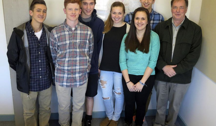 ADVANCE FOR RELEASE SUNDAY, APRIL 19, 2015, AT 12:30 A.M. EDT. AND THEREAFTER -  In this March 24, 2015 photo, HotFutbol President John Evans, right, poses with student soccer players, who will travel to Haiti to help support an after school soccer education program, in Pittsfield, Mass. From left are students Nico Terpak, Michael Peplowski, Jamie Rosiello, Jamie McMahon, Angela Petretta and Jackson Rich. (Jenn Smith/The Berkshire Eagle via AP)