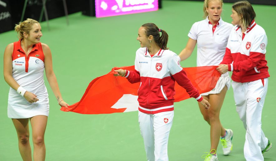 Switzerland's Timea Bacsinszky, left, Martina Hingis, second from, Viktorija Golubic, third from left, and Stefania Voegele celebrate their win over Poland in the Fed Cup World Group Playoff tennis match between Poland and Switzerland, in Zielona Gora, Poland, Sunday, April 19, 2015. (AP Photo/Alik Keplicz)