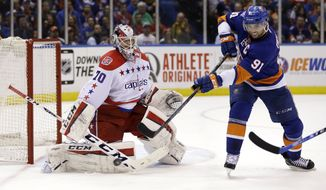 Washington Capitals goalie Braden Holtby, left, blocks a shot by New York Islanders' John Tavares during the second period of Game 3 of a first-round NHL hockey playoff series, Sunday, April 19, 2015, in Uniondale, New York. (AP Photo/Seth Wenig)