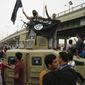 Islamic State militants raise their flag as they patrol in a commandeered Iraqi military vehicle in Fallujah, Iraq. (Associated Press)