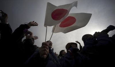 Well-wishers wave Japanese flags to greet Japan's Emperor Akihito and Empress Michiko during New Year's public appearance of the imperial couple at the Imperial Palace in Tokyo on Jan. 2. (Associated Press)