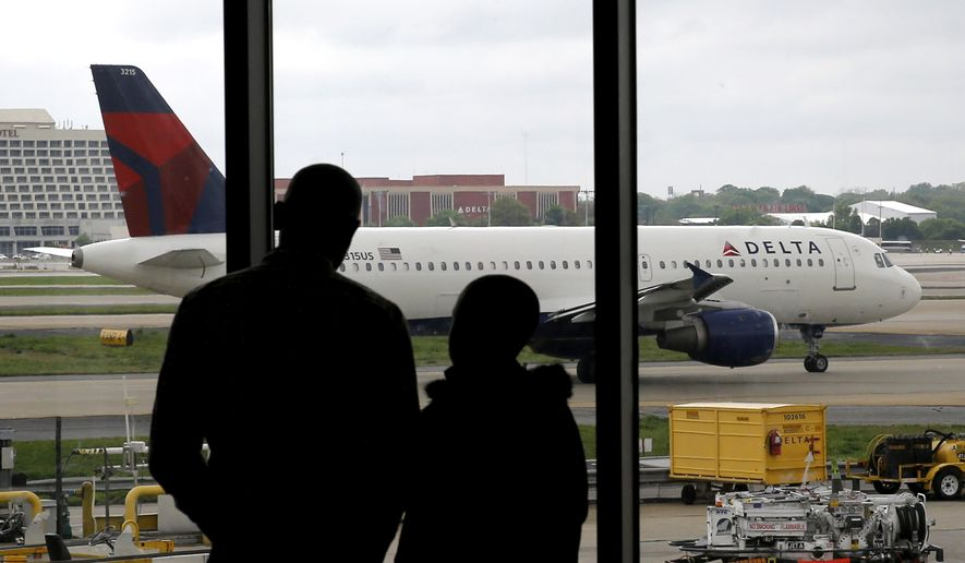 Travelers watch as a plane taxis at Hartsfield-Jackson Atlanta International Airport in Atlanta in this Tuesday, April 14, 2014, file photo. (AP Photo/Charles Rex Arbogast)
